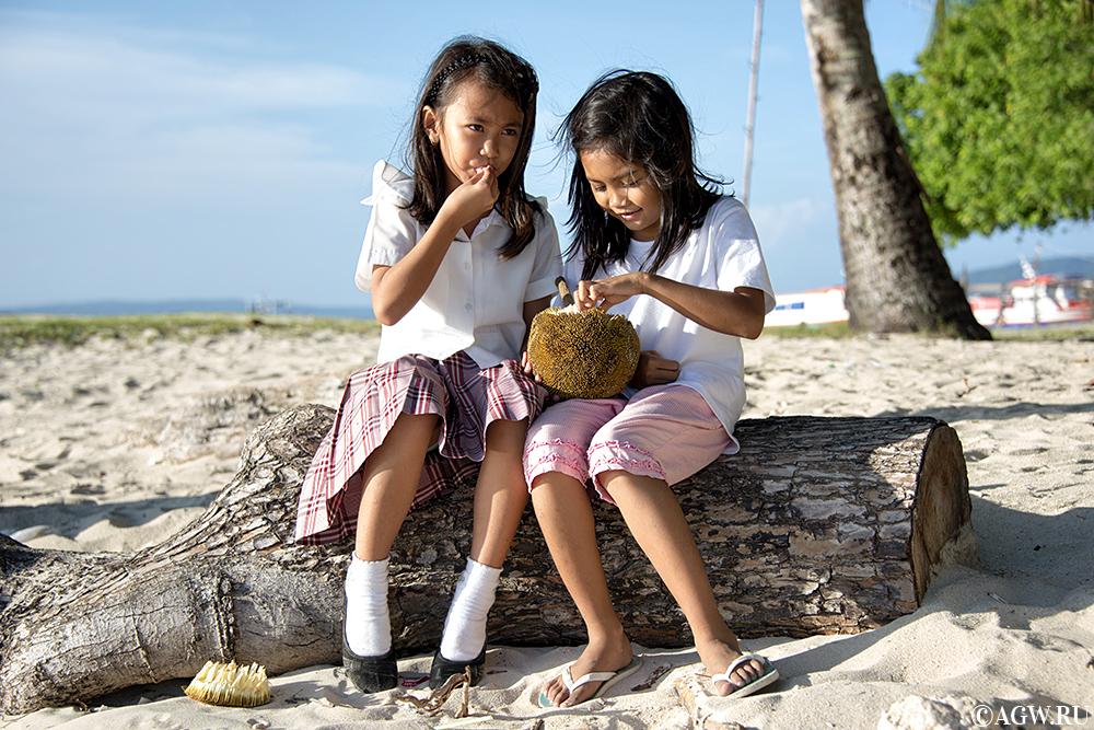 Филиппинские девочки едят маранг на берегу моря.